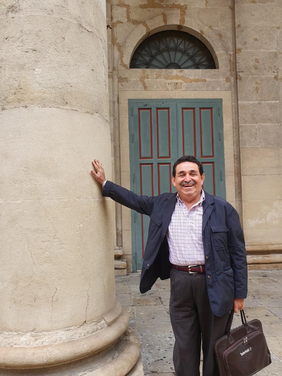 Manuel Mestre, sonriente y tocando una de las columnas de la fachada del Teatro Principal de Alicante / Alex Ferrer