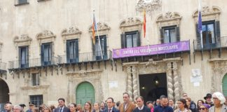 Miembros de la corporación municipal y de la sociedad civil guardando el minuto de silencio con la fachada de Ayuntamiento de Alicante de fondo/ Alex Ferrer